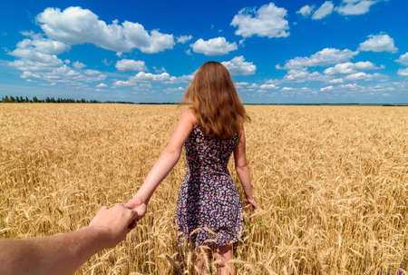 Follow me. Beautiful young brunette woman holding man hand in wheat field with cloudy blue sky background, free space. Couple walking hand in hand in wheat field. Travel and journey concept