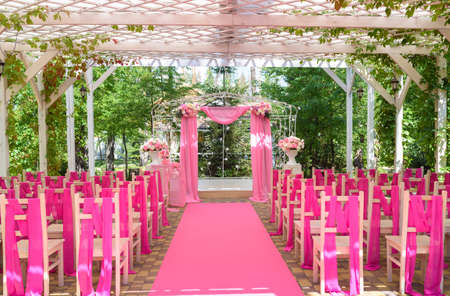 Place for wedding ceremony in pink color with wedding arch decorated with flowers and pink cloth and wooden chairs for guests on each side outdoors. Beautiful wedding archway with chairs on each side