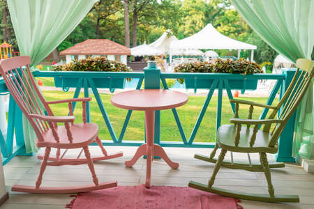 Pink And Green Wooden Rocking Chairs And Table On Porch Or Balcony. Two  Relaxing Armchairs