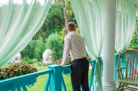 Back view of young man dressed in white shirt and black trousers on porch outdoor, free space. Groom standing on wooden terrace with green nature view. Bussines man  enjoying the view from balcony