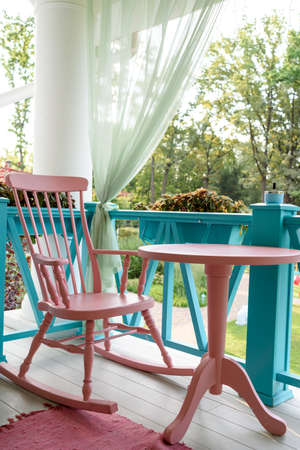 Pink wooden rocking chair and table on porch or balcony. One relaxing armchair on porch of luxury hotel. Empty cafe with rocking chair and table on summer terrace outdoor, free space