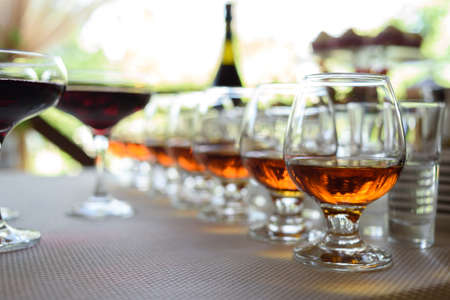 Row of glasses with whiskey or cognac on the table, free space. Strong alcohol in bar or restaurant. Transparent glasses with alcoholic drink Stock Photo