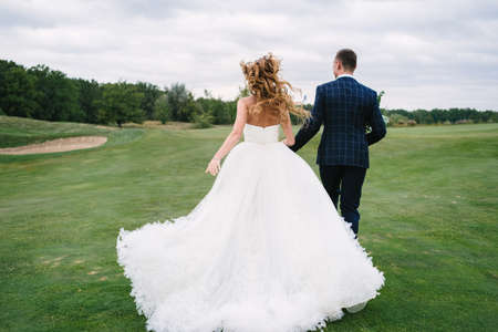 Full length body portrait of young bride and groom running on green grass of golf course, back view. Happy wedding couple walking through golf course