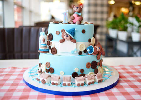 Round multi tiered blue  birthday cake decorated with button, toys, bears, locomotive and number one on the top, copy space for text