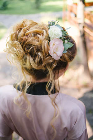 Beautiful bride in silk robe with fashion wedding hairstyle with fresh flowers, back view. Blond girl with curly hair styling. Hairstyle for long hair