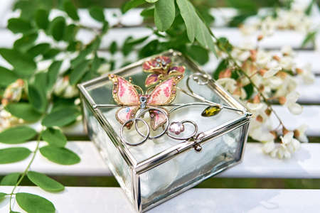 Two golden wedding rings on glass box with butterfly and branch of white acacia with flowers and leaves on wooden surface.