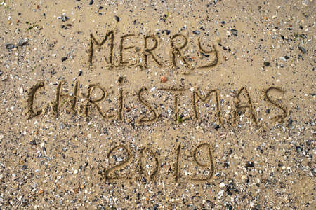 Merry Christmas written on tropical beach sand, copy space. Holiday concept, top view Stock Photo