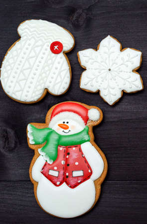 Christmas background with tasty homemade gingerbread cookies with icing on wooden table, top view, flat lay. Snowman, snowflake, mitten. Christmas food, copy space 스톡 콘텐츠