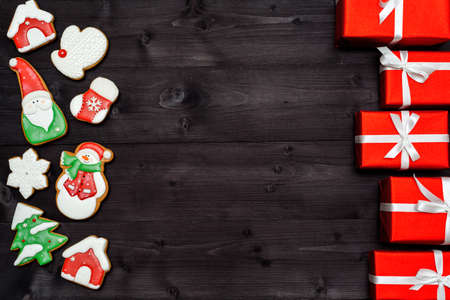 Christmas background border with tasty homemade gingerbread cookies and red gift boxes on wooden table, top view, flat lay. Christmas food, copy space. Christmas decorations