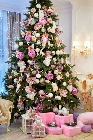 Christmas background with big Christmas fir tree with white and pink decorations at home indoors, copy space. Winter holidays, family concept 스톡 콘텐츠