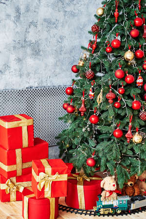 Christmas background with Christmas fir tree, red gift boxes decorated with golden ribbon and child toys on floor, copy space. Winter holidays concept 스톡 콘텐츠