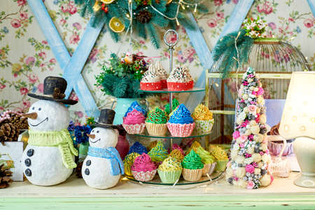 Christmas background with snowman, decorated Christmas tree and colorful cupcakes on wooden table, copy space. Festive snowmen with Christmas decorations