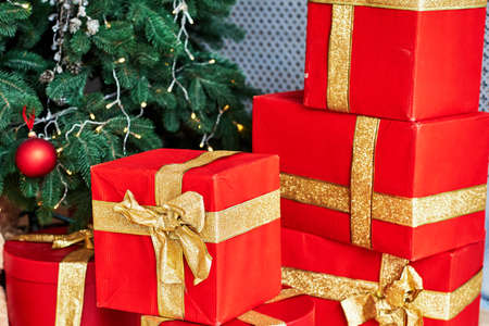 Christmas background with red gift boxes decorated with golden ribbon on floor under Christmas tree, copy space. Winter holidays concept