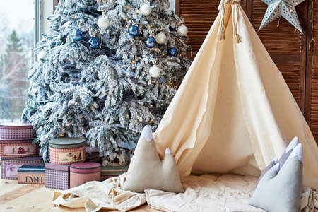 Christmas tree with gifts and wigwam near window in child room, copy space. Christmas decorations. Childen room interior with decorated play tipi tent. Scandinavian style 스톡 콘텐츠