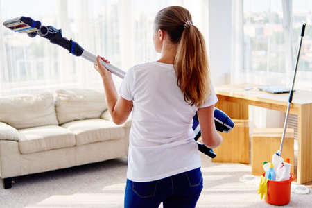 Portrait of young woman in white shirt and jeans holding in hands wireless vacuum cleaner while cleaning in living room at home, copy space. Housework, cleanig and chores concept 스톡 콘텐츠