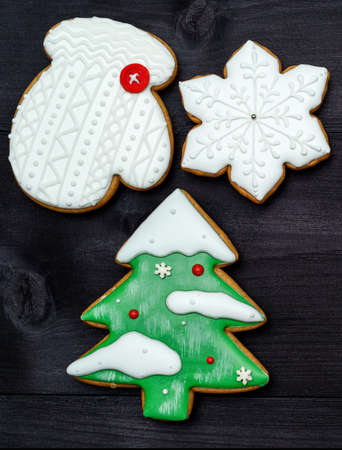 Christmas background with tasty homemade gingerbread cookies with icing on wooden table, top view, flat lay. Christmas tree, snowflake, mitten. Christmas food, copy space