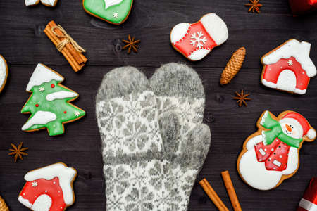 Christmas background with tasty homemade gingerbread cookies and knitted mittens on wooden table, top view, flat lay. Fir tree, snowman, house, mitten, cinnamon. Christmas decorstions, copy space