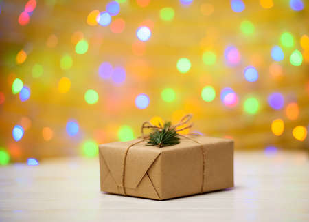 Christmas background with one gift box wrapped in kraft paper with fir tree branch on golden blured, sparkling background, copy space. Holiday greeting card