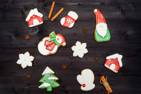 Christmas background with tasty homemade gingerbread cookies on wooden table, top view, flat lay. Christmas tree, snowflake, house, santa, mitten, sock, cinnamon. Christmas food, copy space 스톡 콘텐츠
