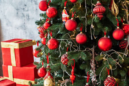 Christmas background with Christmas tree and red gift boxes decorated with golden ribbon, copy space. Winter holidays concept