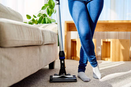 Close up of young woman in jeans cleaning carpet with vacuum cleaner in living room, copy space. Housework, household, spring-cleanig and chores concept. House cleaning