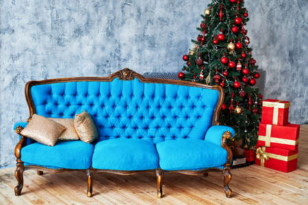 Christmas morning, copy space. Classic apartments with blue buttoned sofa, decorated fir tree and red gift boxes. Christmas interior