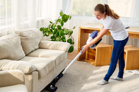 Full length body portrait of young woman in white shirt and jeans cleaning carpet with vacuum cleaner in living room, copy space. Housework, cleanig and chores concept Stock Photo