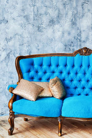 Classic vintage blue buttoned sofa with golden cushions on gray concrete wall indoors, copy space. Living room interior 스톡 콘텐츠