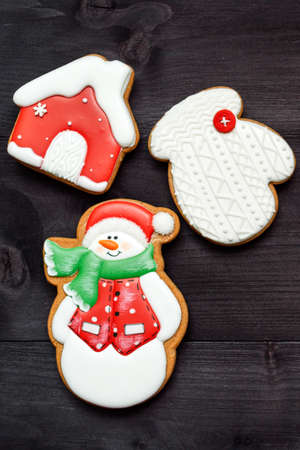 Christmas background with tasty homemade gingerbread cookies with icing on wooden table, top view, flat lay. Snowman, snowflake, house. Christmas food, copy space 스톡 콘텐츠
