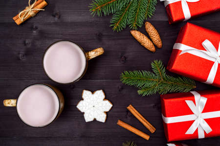 Top view of two cups of hot cocoa, ginger snowflake cookie, red gift boxes and fir tree branches on wooden background, copy space. Christmas background, free space. Flat lay, above, overhead 스톡 콘텐츠