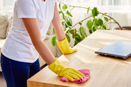 Cropped image of woman in white shirt and yellow protective rubber gloves cleaning at home and wiping dust on wooden tablel with pink rag, copy space. Housework, cleanig and chores concept