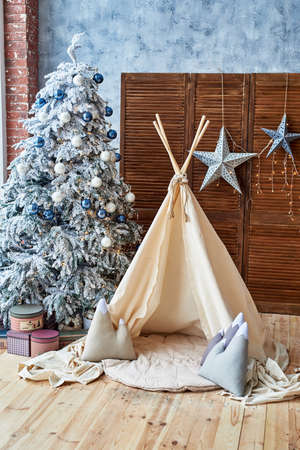 Christmas tree with gifts and wigwam in child room, copy space. Christmas decorations. Childen room interior with decorated play tipi tent. Scandinavian style