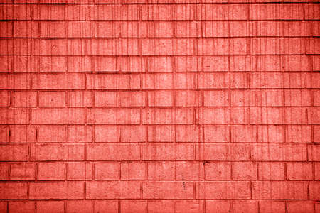 Living Coral background of grunge brick wall texture; copy space. Color of the year 2019. Top view; flat lay