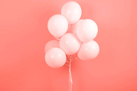 Living Coral background with bunch of flying balloons, copy space for text. Color of the year 2019. Christmas, birthday, valentine, wedding, holiday concept