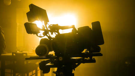 movie camera on the slider in the backlight from the window, the rays of the sun in a smoky room Foto de archivo