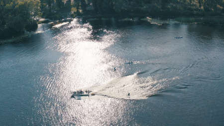 sunny summer day over green islands on a river in a northern city, people actively spend time on the river, kayaking and wake boarding, wake surfing after fast boats - Aerial Fligh Foto de archivo