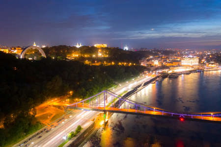 night cityscape. aerial view. colorful led bridge across river and quay road in Kyiv