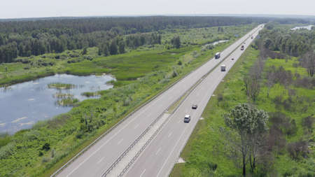 two cars drive each other along the road that is surrounded by forests, lakes, fields and meadows. retro cars and modern minivans travel in summer. aerial view
