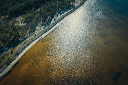 top view of the shoreline and colored water of the reservoir. stones, sand, pines, water. abstract shot of the green northern Pine forests, lungs of the planet, on the bay - Aerial Flight Foto de archivo