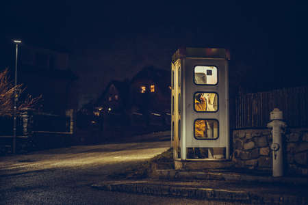 the girl speaks in the night telephone booth. mystical and mysterious street phone. dangerous place on an empty street