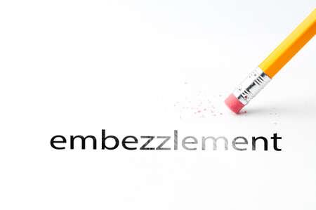 Closeup of pencil eraser and black embezzlement text. Embezzlement. Pencil with eraser. Stock Photo