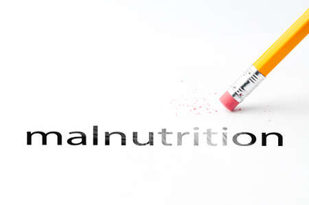 eradicate: Closeup of pencil eraser and black malnutrition text. Malnutrition. Pencil with eraser. Stock Photo