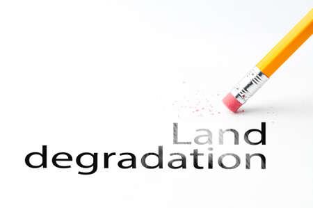 degradation: Closeup of pencil eraser and land degradation text. Land degradation. Pencil with eraser.