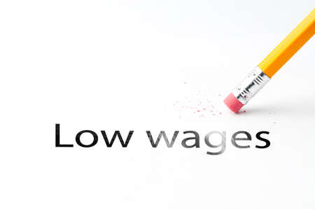 Closeup of pencil eraser and black low wages text. Low wages. Pencil with eraser.