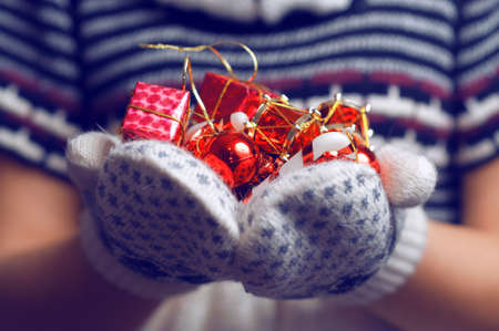 adult christmas: Woman holding a Christmas Decorations. Christmas Background. Gift box. Knitted mittens. Happy Holidays. Knitted dress. Toned image
