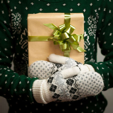 Christmas gifts. Knitted mittens. Knitted dress. Box with gifts. Present.