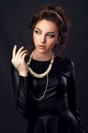 20 29 years: Beautiful young woman. Young girl. Girl in leather clothes. Portrait on a dark background. Beauty portrait. Toned image Stock Photo