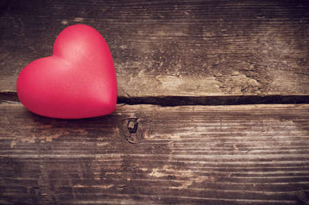 s shape: Valentine day. Red hearts on the old dark boards. Valentines Day. Heart pendant. Red heart.  Space for text. Eighth of March. International Womens Day. Small DOF. Toned image. Stock Photo