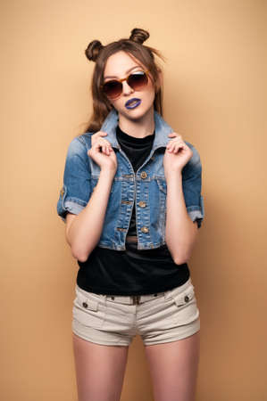 chinese american ethnicity: Beautiful young woman Chinoise in sunglasses. Spring-summer outfit. Hairstyle Coachella. Denim Jacket, dark lipstick. Cute Chinese, Asian-Caucasian woman, fashionable . Yellow background. Toned image.