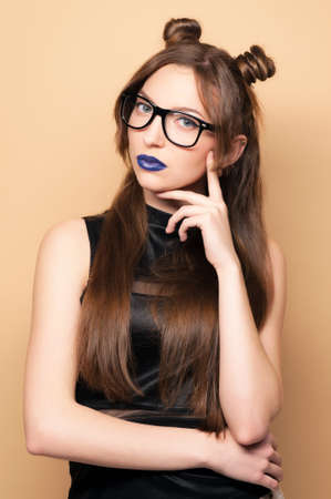 chinese american ethnicity: Beautiful young woman in glasses. Cut girl. Spring-summer outfit. Hairstyle Coachella. Short Sexy Shorts. Dark blue lipstick. Fashionable  woman . Yellow background. Toned image.